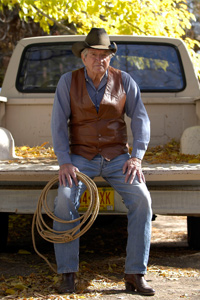 Author Max Evans sits on the tailgate of his pick-up truck outside his house in Albuquerque, N.M., on Nov. 22, 2003.