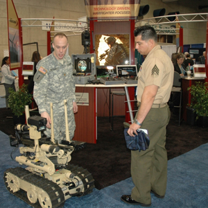 Maj. Michael Pottratz (L), explosive ordnance disposal deputy director of technology for the U.S. Armament Research, Development and Engineering Center, explains the functions of the SWORDS robot at a technology conference in 2008.