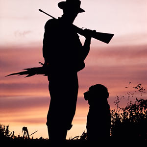 Silhouette of hunter holding rifle standing with dog.