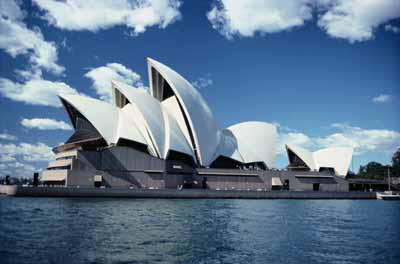 With distinctive roofs shaped like sails, the Sydney Opera House stands on Bennelong Point in Sydney Harbor.
