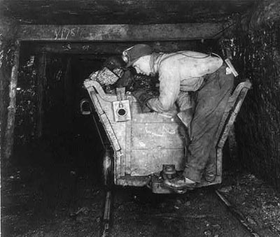 A coal miner standing on the back of a car in a mine tunnel