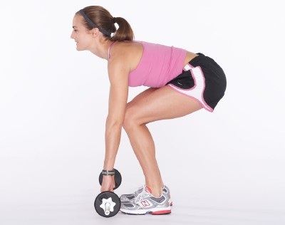 Keeping dumbbells close to body, bend at knees and slowly lower dumbbells toward floor.